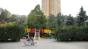 Dziewczyna z złamaną nogą siedzi w wózku inwalidzkim przed boiskiem zbiory