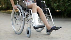 Dziewczyna z złamaną nogą w wózku inwalidzkim zdjęcie wideo