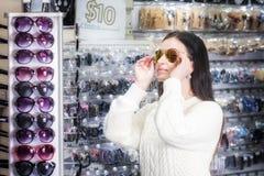 Dziewczyna zakupy okulary przeciwsłoneczni w sklepu rynku Obrazy Royalty Free