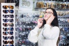 Dziewczyna zakupy okulary przeciwsłoneczni w sklepu rynku Fotografia Stock