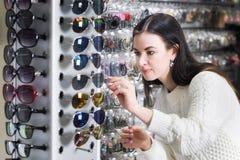 Dziewczyna zakupy okulary przeciwsłoneczni w sklepu rynku Zdjęcia Royalty Free