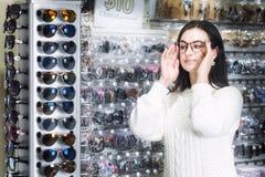 Dziewczyna zakupy okulary przeciwsłoneczni w sklepu rynku Obrazy Stock