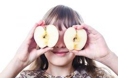 Dziewczyna zamykająca przygląda się dwa segmentu jabłko Obrazy Royalty Free