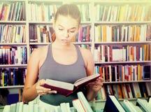 Dziewczyna zaskakująca książka w bibliotece Fotografia Stock