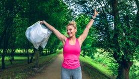 Dziewczyna zbroi w górę pokazywać torba na śmiecie robi plogging Fotografia Stock
