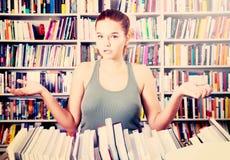 Dziewczyna zdumiony wybór książki w bibliotece Fotografia Royalty Free