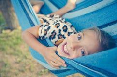 Dziewczynka śmia się na słonecznym dniu Kłama w błękitnym hamaku szczęśliwy mały dziecka Zdjęcie Royalty Free