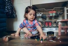 Dziewczynka bawić się z włosianymi klamerkami siedzi w podłoga Zdjęcie Royalty Free