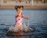 Dziewczynka bawić się z wodą w morzu Zdjęcie Stock