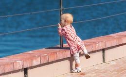 Dziewczynka na kamiennym jetty rzeką Fotografia Stock
