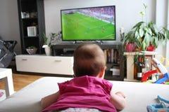 Dziewczynka ogląda piłkę nożną na TV Obrazy Royalty Free