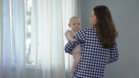 Dziewczynka patrzeje w kamerę i macha ręki, kochający macierzysty pociesza dziecko zdjęcie wideo