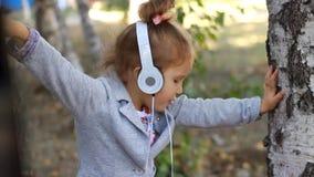 Dziewczynka słucha muzyka i śpiew w hełmofonach piosenka w parku z brzozami zbiory wideo