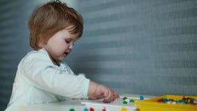 Dziewczynka siedzi przy childs stoły i zbiera mozaikę w zwolnionym tempie, uśmiech