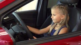 Dziewczynka siedzi przy kierownicą i udaje jechać zbiory
