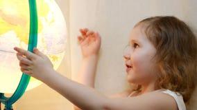 Dziewczynka studiuje świat i kulę ziemską Dzieci spojrzenia przy przedstawieniami i mapą miejsce przyszłościowa podróż zdjęcie wideo