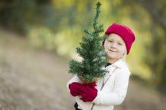 Dziewczynka Trzyma Małej choinki W Czerwonych mitynkach i nakrętce Zdjęcie Royalty Free