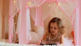 Dziewczynka używa pastylkę w sypialni Dziecko ogląda wideo na ekranie komputerowym i bawić się w jej pokoju zbiory wideo