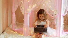 Dziewczynka używa pastylkę w sypialni Dziecko ogląda wideo na ekranie komputerowym i bawić się w jej pokoju zdjęcie wideo
