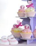 Dziewczynka łupy na purpurowym babeczka stojaku i babeczki Zdjęcia Royalty Free