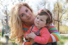 Dziewczynka wącha magnoliowego okwitnięcie z matką w wiośnie Fotografia Stock