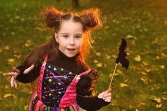 Dziewczynka w karnawałowym kostiumu z magiczną różdżką z nietoperzem i obraz stock