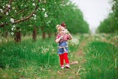 Dziewczynka w kwiatonośnej wiośnie uprawia ogródek dandelions Fotografia Stock