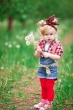 Dziewczynka w kwiatonośnej wiośnie uprawia ogródek dandelions Zdjęcia Royalty Free