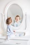 Dziewczynka z kędzierzawego włosy kolejną rundą w lustrze zdjęcia royalty free
