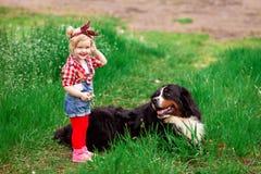 Dziewczynka z psim Bern w wiosna ogródzie Zdjęcia Stock