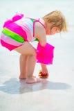 Dziewczynka znajdująca skorupa na dennym brzeg odosobniony tylni widok biel Zdjęcie Royalty Free