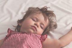 Dziewczynki dosypianie na plecy z otwartymi rękami bez pacyfikatoru w łóżku z białymi prześcieradłami i Pokojowy dosypianie w jas obraz stock