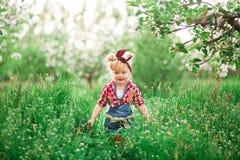 Dziewczynki wiosna uprawia ogródek dandelions Zdjęcie Stock
