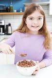 Dziewczyny łasowania puchar Cukierkowy Śniadaniowy zboże W kuchni Obrazy Stock