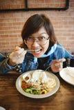 Dziewczyny łasowania wieprzowina smażący ryż W restauraci zdjęcie royalty free
