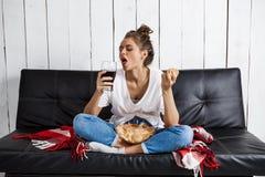 Dziewczyny łasowanie szczerbi się, pijący sodę, oglądający tv, siedzi przy kanapą obrazy royalty free