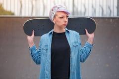 Dziewczyny łyżwiarka trzyma deskorolka za ona z powrotem i spojrzenia strona w jeździć na łyżwach parka fotografia stock