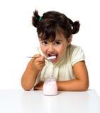 Dziewczyny łasowania jogurt Fotografia Stock