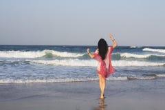 Dziewczyny brunetka w czerwonej tunice, złociste bransoletki wchodzić do w oceanie indyjskim Zdjęcie Royalty Free