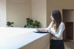 Dziewczyny brunetki studencki writing w notatniku fotografia stock