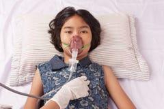 Dziewczyny choroba w inhalator maski dzieciaka lying on the beach na Cierpliwym ` s łóżku Fotografia Royalty Free