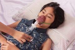 Dziewczyny choroba w inhalator maski lying on the beach na Cierpliwym ` s łóżku Obrazy Stock