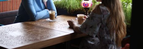Dziewczyny cieszy się w kawiarni wpólnie Młode kobiety spotyka w kawiarni spotykać dwa kobiety w kawiarni dla kawy błękit suknia, obrazy royalty free