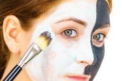 Dziewczyny czerni maska na przyrodniej twarzy stosuje bia?ego b?oto obrazy stock