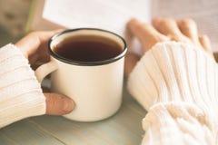 Dziewczyny czytelnicza książka i pić herbata w zimie Zdjęcie Royalty Free