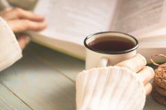 Dziewczyny czytelnicza książka i pić herbata w zimie Obrazy Stock