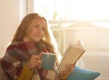 Dziewczyny czytelnicza książka i pić w domu herbata Obrazy Royalty Free