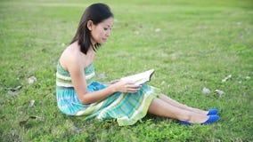 Dziewczyny czytelnicza książka w parkowy ono uśmiecha się zbiory wideo