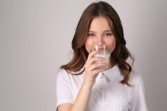 Dziewczyny degustaci mleko z bliska Biały tło Obrazy Royalty Free