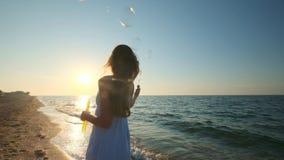 Dziewczyny dmuchanie gulgocze na plaży w zwolnionym tempie Młoda dziewczyna dmucha mydlanych bąble w wieczór, podczas zmierzchu B zbiory wideo